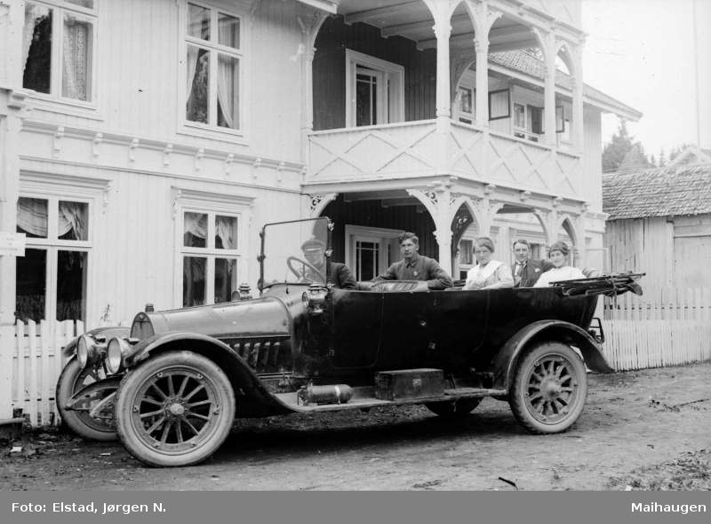 Bil av merke Opel med nedslått kalesje og fem personer foran Grand Hotel på Jørstadmoen