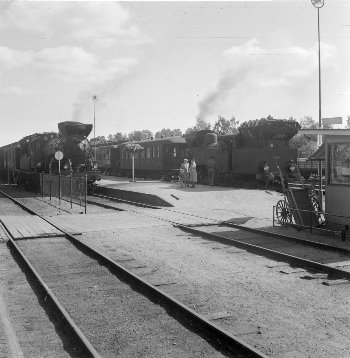 Två ånglok med vedeldning står vid plattformen vid Söderhamn station.