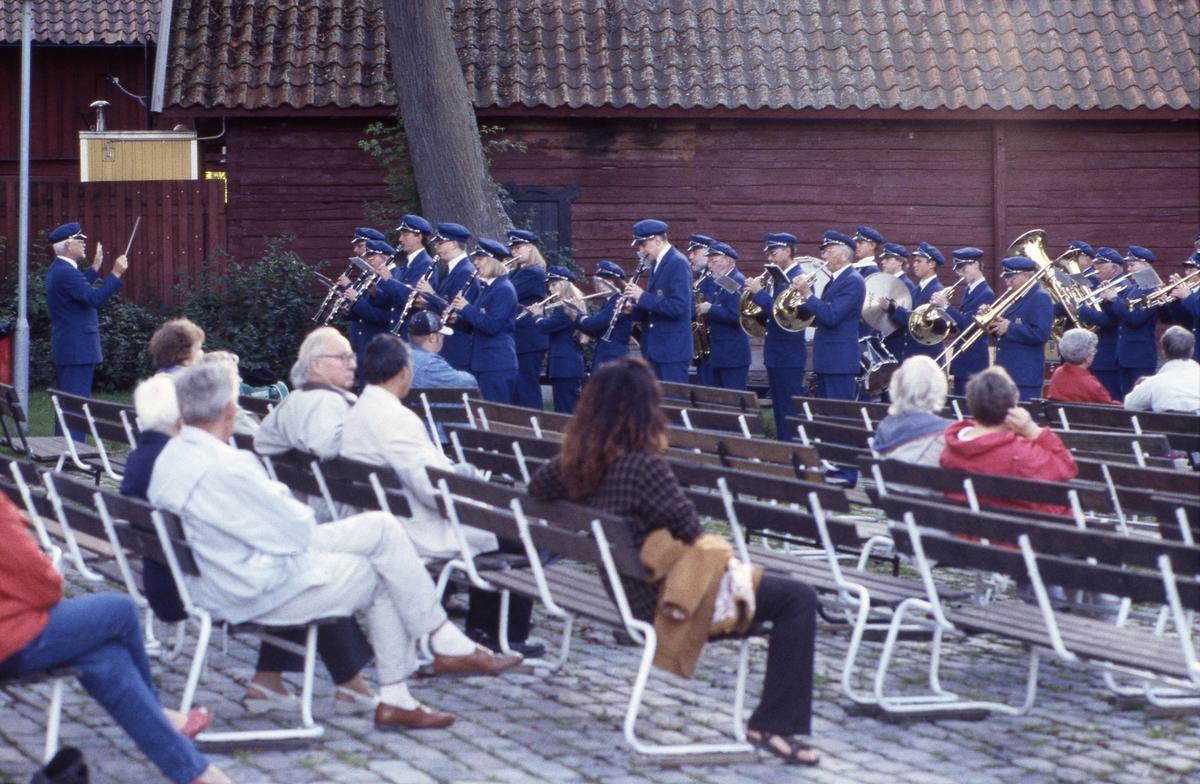 Håkan Harrysson dirigerar Arboga Blåsorkester. De uppträder i samband med sommaravslutningen i Olof Ahllöfs park. Sparsamt med publik i bänkarna.