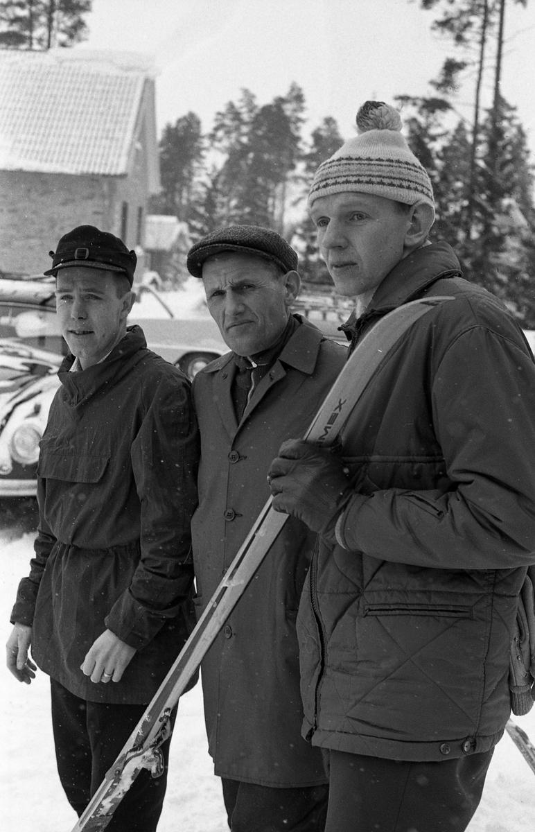 Skidtävlingen AT-loppet. Tre män i ytterkläder. Mannen som håller i skidan är Hans Ekberg. I bakgrunden syns ett hus och en folkvagn. (AT kan betyda Arboga Tidning)