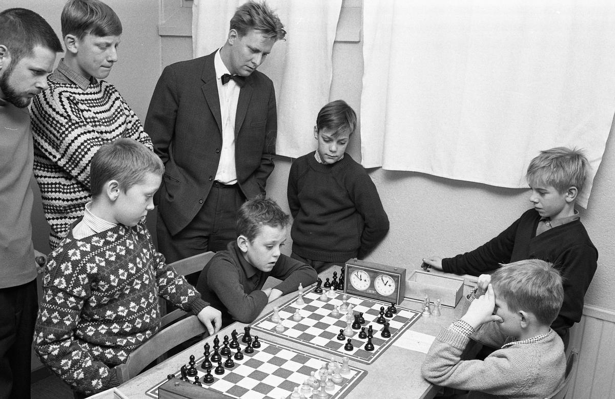 AT-schack. Två pojkar spelar schack. Tre män och tre pojkar ser på. En av männen bär kavaj och fluga. Mannen längst till vänster är Göran Malmsten och pojken längst till höger, i mörk tröja, är Ulf Andersson. (AT kan betyda Arboga Tidning)