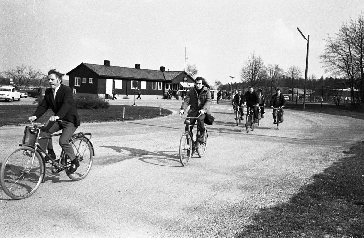 Arbetsdagen är slut. Män cyklar hem från CVA, Centrala Verkstaden Arboga. I bakgrunden ses bilparkeringen, byggnaden där vakten sitter och har kontroll på grinden som alla måste passera.