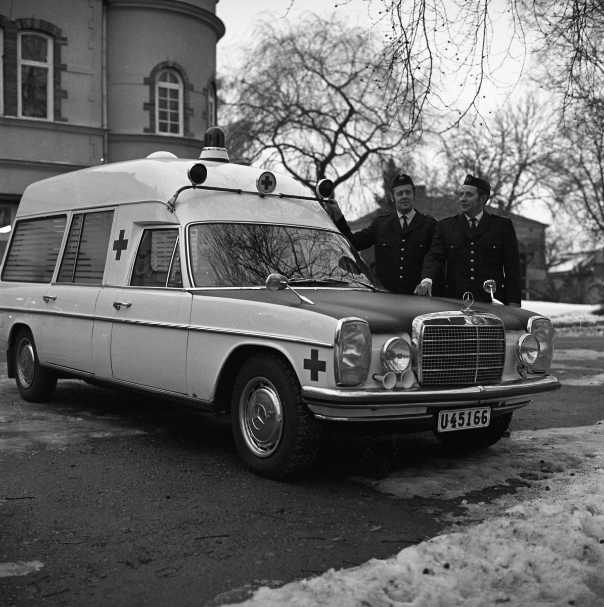 Ny ambulans. De uniformerade herrarna är Ingemar Wiberg och Rolf Persson. Bilden är tagen utanför brandstationen på Strandvägen.
