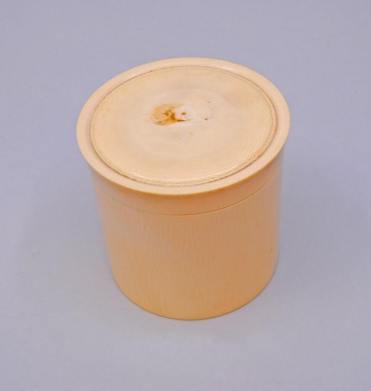 Gräddvit, cylindrisk burk (A) av elfenben med lock (B), samt ett inre lock (C). Mitt på locket finns två hål där det troligtvis suttit en kungakrona i relief. Runt hålen finns en instansad ring.   Det yttre locket skruvas av, medan det lock som finns i burken lyfts. Det inre locket är tunnare och har en knapp att lyfta i. På det yttre locket finns bågformade mönster som överlappar varandra.
