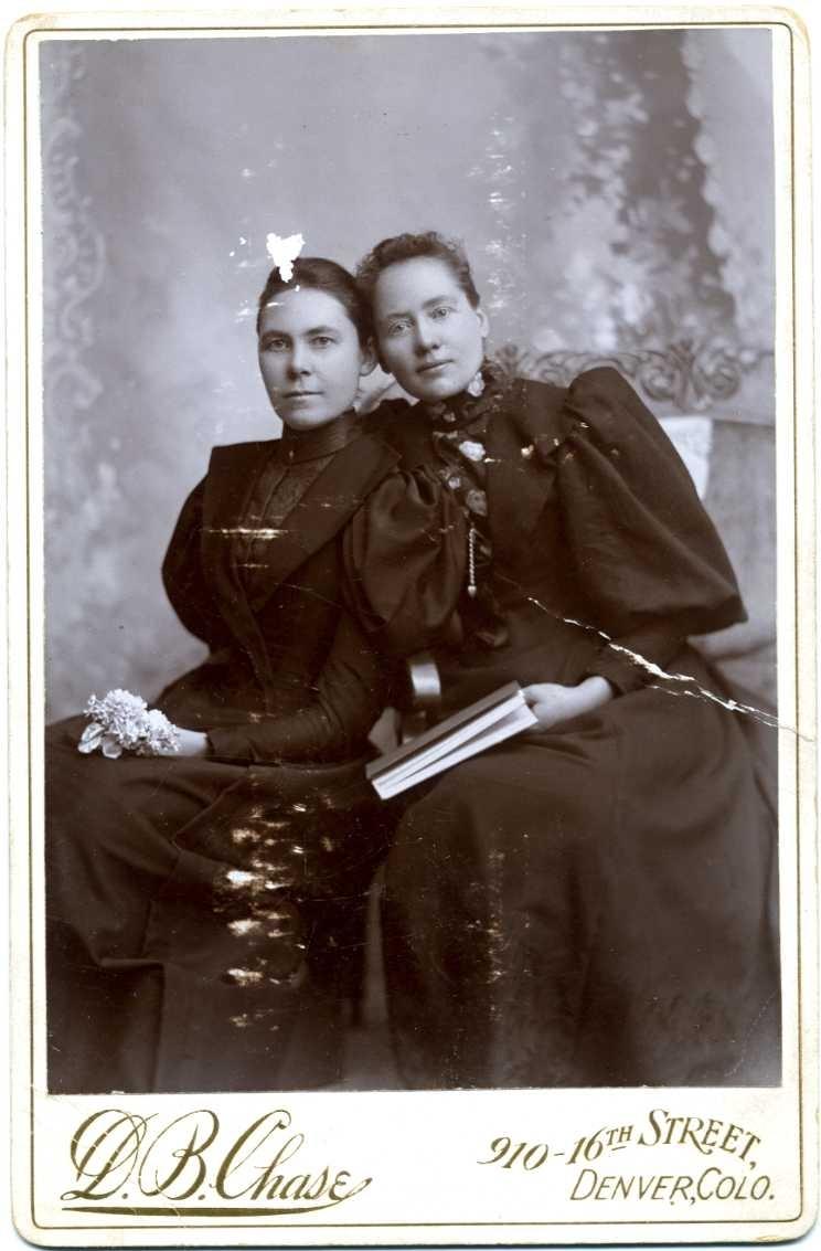 Kabinettsfotografi: gruppbild med två unga kvinnor i mörka klänningar som sitter lutade mot varandra. En kvinna har en blomma i knät och den andra kvinnan håller i en bok.