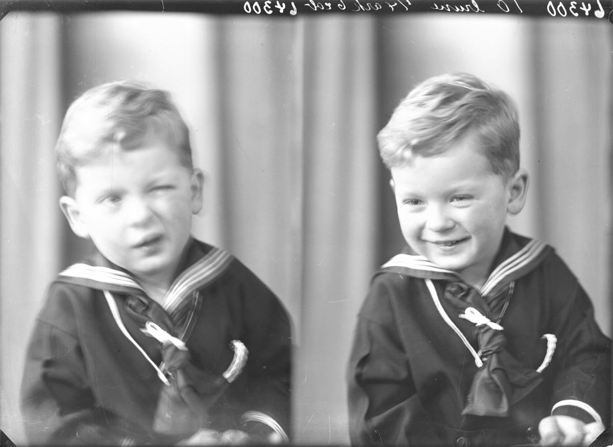 Portrett. Liten lyshåret gutt i mørk marineuniform sittende på en hvit gyngehest. Bestillt av Fru Lorens Nilsen, Haselt 18