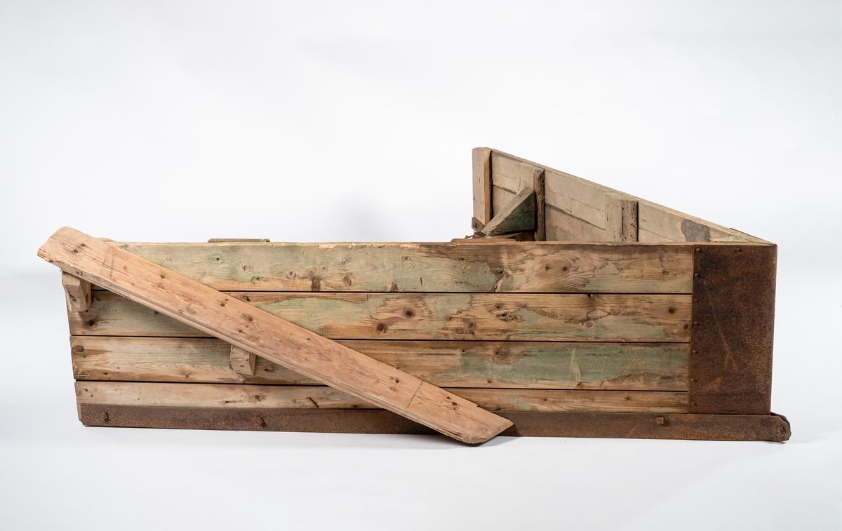A-formet snøplog i tre. Plogen er laget av grovt materiale. Skjæret består av 4 bord lagt oppå hverandre. På innsiden av plogen er det festet to tverrbjelker i tre. På undersiden av tverrbjelkene er det skrudd fast et jern som er formet til en firkant. På den bakerste tverrbjelken er det festet en metallhempe i hver side, som har hver sin kjetting tredd på. Den bakerste tverrbjelken er forsterket med treklosser i hver side, og med avstivere i metall på baksiden. Den nedre kanten innvendig er forsterket med treplanker. Utvendig er plogen forsterket med metallskoning langs skjærets nederkant, og med en metallplate i skjærets spiss. På plogens ene side er det spikret på en veltefjøl av tre, denne skrår oppover bak. Treverket har grønnskjær og er muligens impregnert.
