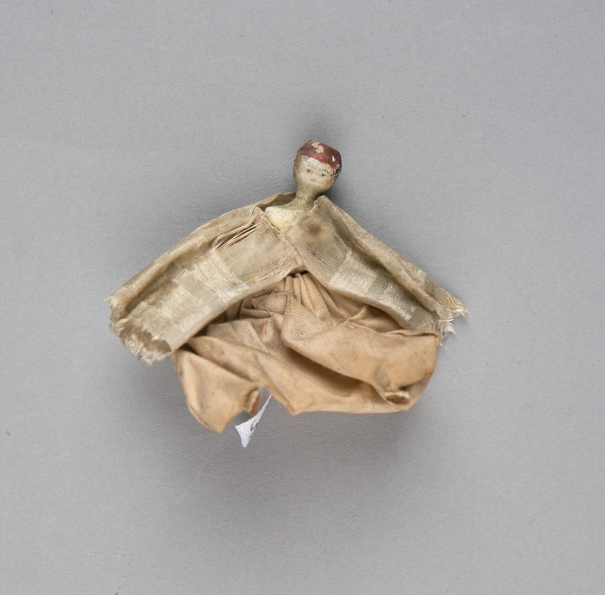 Dokke. Del av lystfartøy fra Østen. Liten figur i tre og silke som skal forestille mannskapet på en rogalei.