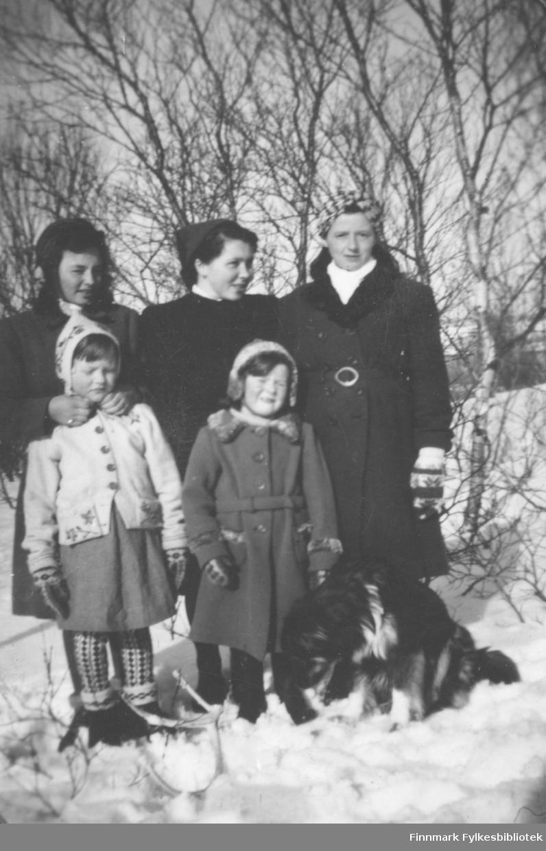 Tre kvinner, to barn og en hund fotografert ute i det snødekte terrenget. De er Grethe Iversen Solstad, Maila Iversen Losoa, Anne Lise Njolla. Barna er Anna Agnethe Mathisen og Ingrid Iversen.