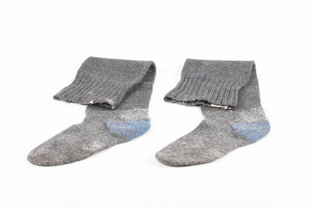 Ett par knestrømper strikket med grått ullgarn. Hælen er strikket med blått garn. På innsiden ved åpningen i begge strømper er det påsydd en lapp med fangenummer.