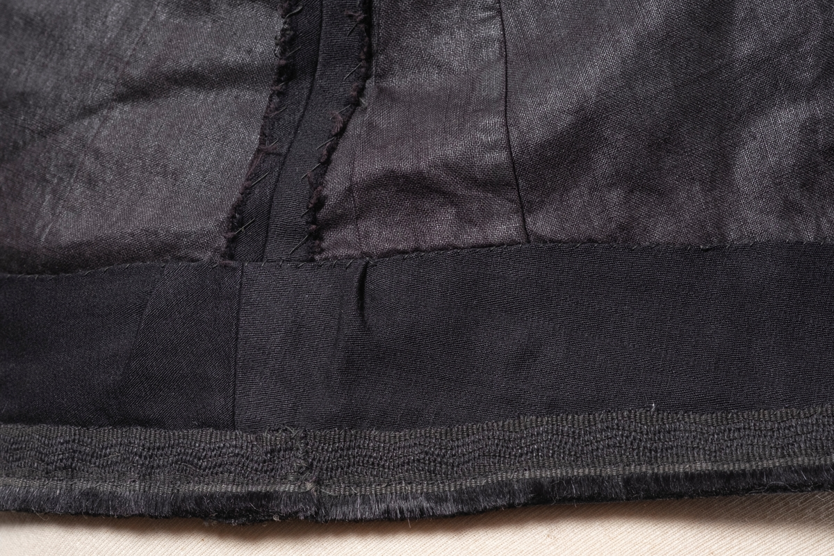 Skjørt i svart bomull som består av et forstykke i tre deler og bakstykke i 4 deler. Skjørtet er fôret med tynn bomull i svart med lilla skjær. Midjen har linning i lilla bomull. Skjørtet har forsterkningskant nederst med slitelist av bånd og floss. Det er påsydd to hemper i linningen. Skjørtet lukkes på baksiden med tre trykknapper. I linnengen er det påsydd en hvit tekstillapp med påskrift.