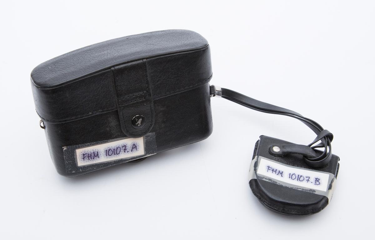 """Kamera i sort skinnetui og beskyttelseslinse i skinnetui med rem satt fast på kamera. Rektangulært kamera. Mrk:""""Minox 35 GL""""."""