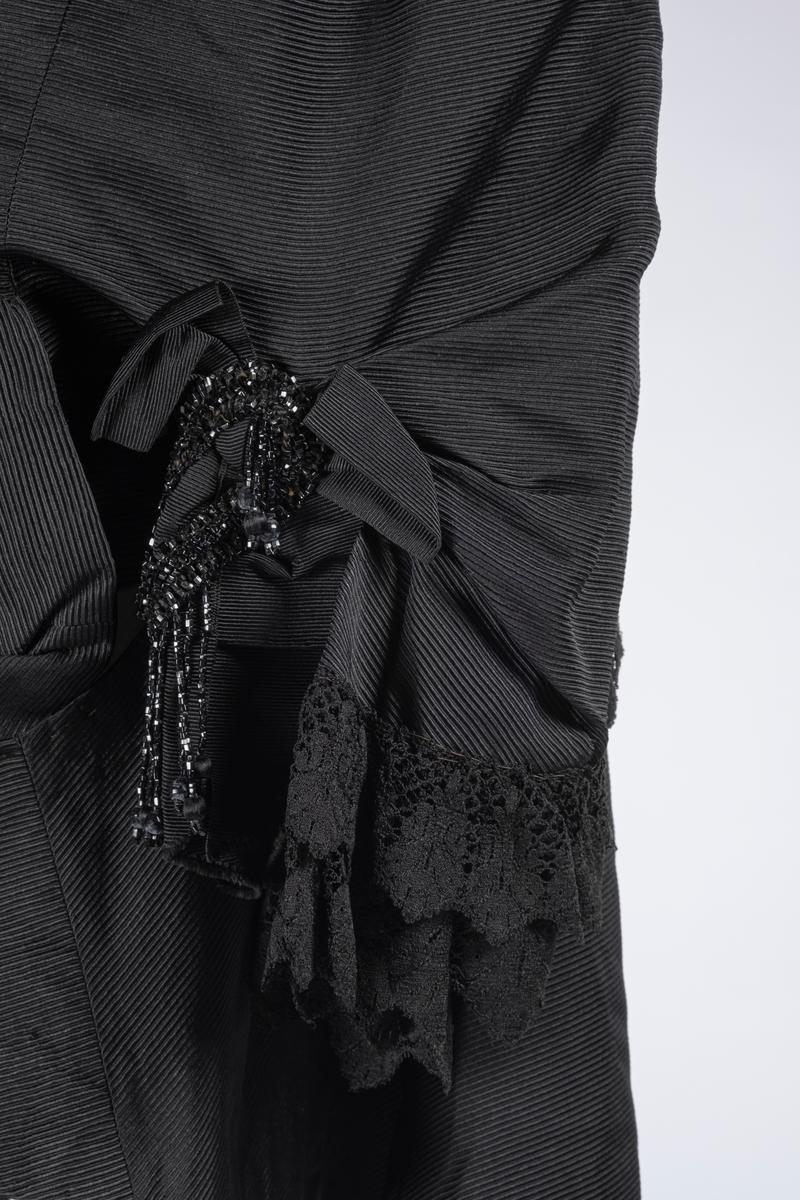 Jakken er ripsvevet og har vide ermer. Det er blonder på ermekantene. På baksiden av ermene er det en sløyfe med perlebrosje og perlefrynser. På framsiden av ermene er det fire perlekvaster. På baksiden av jakken er det perlebroderi med perlekvaster. Jakken er fòret med silke. Jakken lukkes med metallhekter.