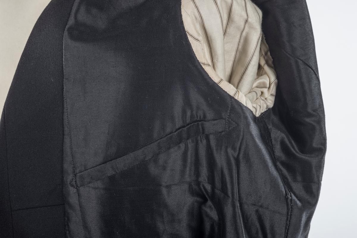 Svart jakke med lange skjøter bak. Den er midjelang foran og litt skrådd mot midten. Den er foret med silke, ermene er foret med bomull. Jakken er dobbeltspent med silketrukne knapper. Det er to mansjettknappet på hver erme. Den har to innerlommer. På baksiden er det to knapper.