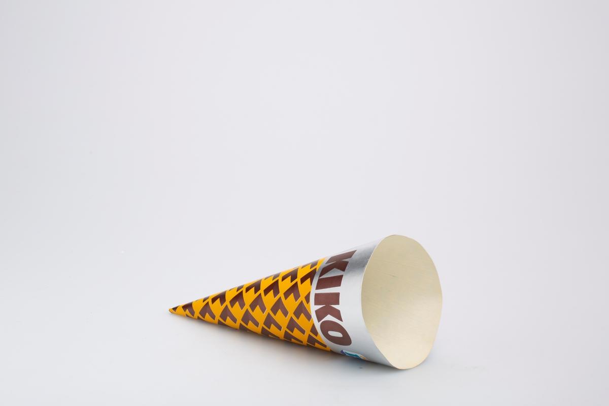Kjegleformet iskrempapir (kremmerhus) i aluminium. Kremmerhuset er med farger på utsiden, og uten farge (hvit) på innsiden. Papiret har sølvfarget felt med tekst øverst. Resten av papiret har repeterende L-formet mønster som trolig skal forestille iskremkjeks.