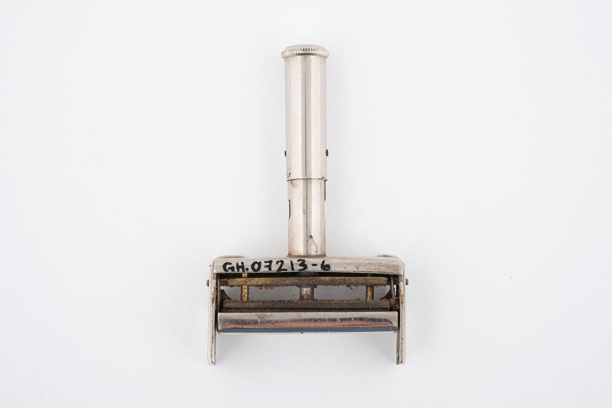 Stempel med stempelpute. Den har fjær i håndtaket for nedpressing av stempelet. Når stempelet presses ned åpner lokket seg.