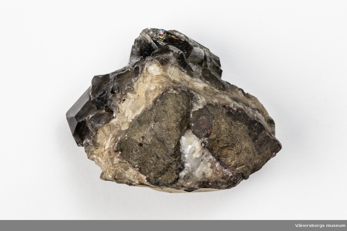Ett mineral som är en kvarts och består av kiseldioxid. Kvartsen har kristallform och färgen är mörk, rökfärgad. Exemplaret kommer från Hässelkulla i Närke, Sverige.