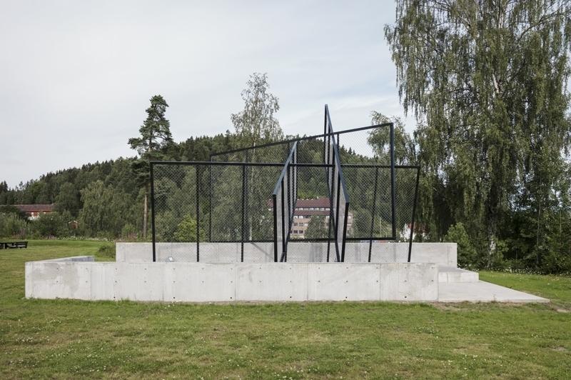 I et uteområde ved NTNU i Gjøvik har Åsdam produsert en høyreist arkitektonisk installasjon basert på helt standardiserte fletteverksgjerde i det offentlige rom. Slike gjerder har gjerne som oppgave å regulere tilgangen til et sted og skille et område fra et annet. I Åsdams kunstneriske bearbeidelse er gjerdene omformet til en skulpturell figur som heller enn å stenge ute skaper et nytt, uventet sosialt rom – et sted hvor folk kan samle seg og utfolde seg. Plassert i nord-vestdelen av campus skaper installasjonen, som både er en skulptur og en plass, sine egne fysiske optiske, og stedsmessige logikker.  Dette verket er en del av prosjektet Migrasjon og arkitektur som gjennom tre kunstprosjekter undersøker relasjonen mellom arkitektur og migrasjon; om hvordan den erfarende kroppen skaper subjektivitet i det offentlige rom.