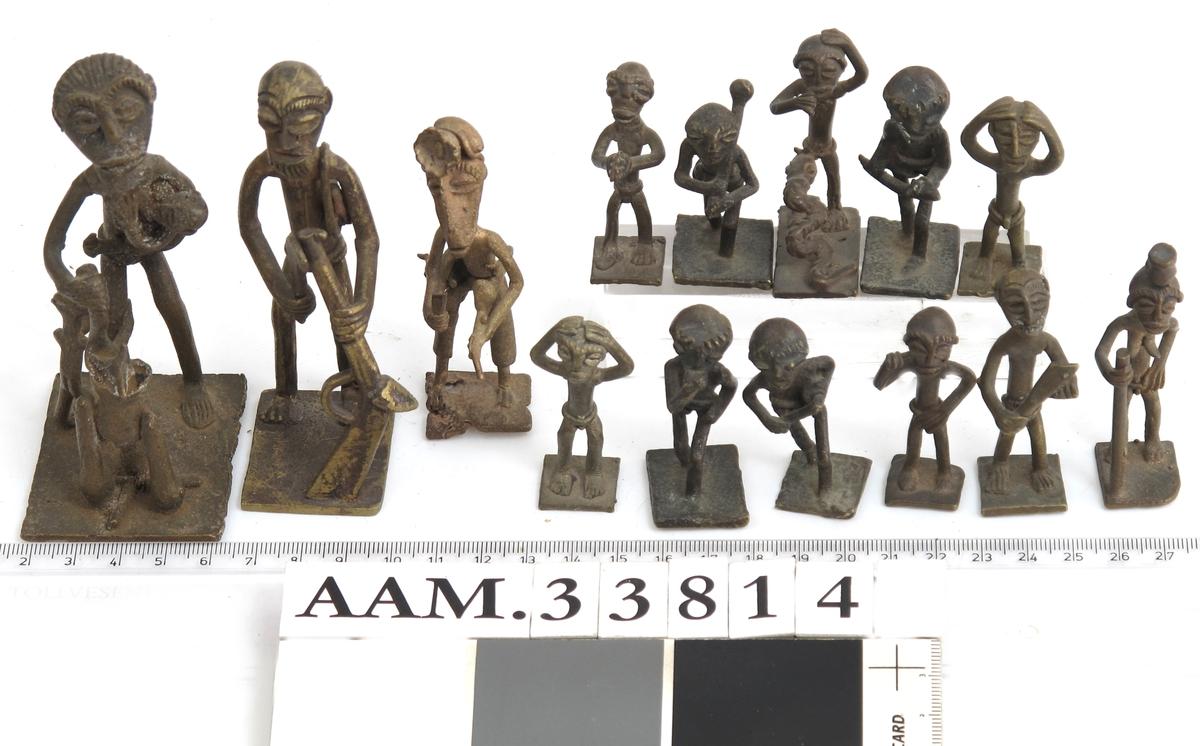 Vektlodd støpt som små, ulike menneskefigurer. Tre noe større, elleve mindre.