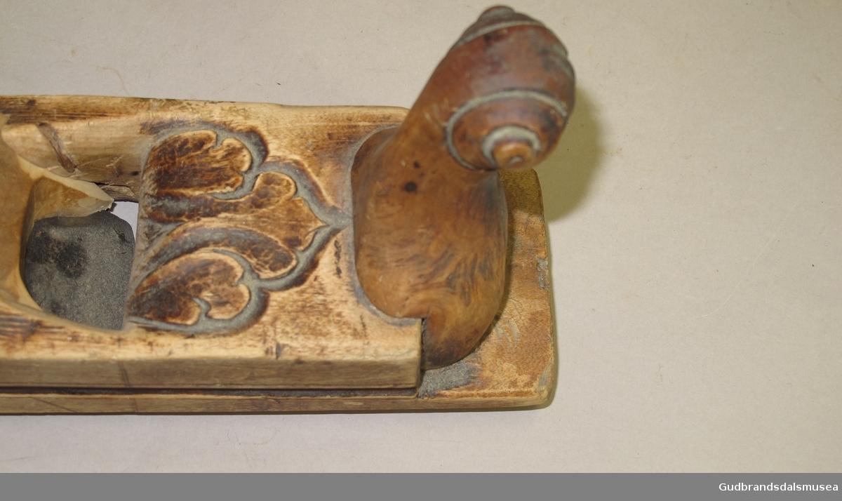 Høvel med konveks tann og høvelstokk. Høvelstokken er pent dekorert med utskjæringer.