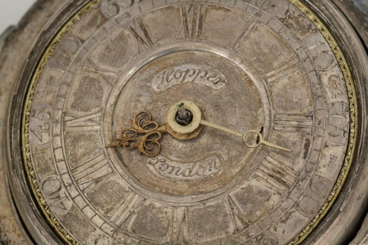 Uret har sølv tallskive med støpte og graverte tall, romertall for timer og alminnelige tall til minutter. Ingen sekundviser.