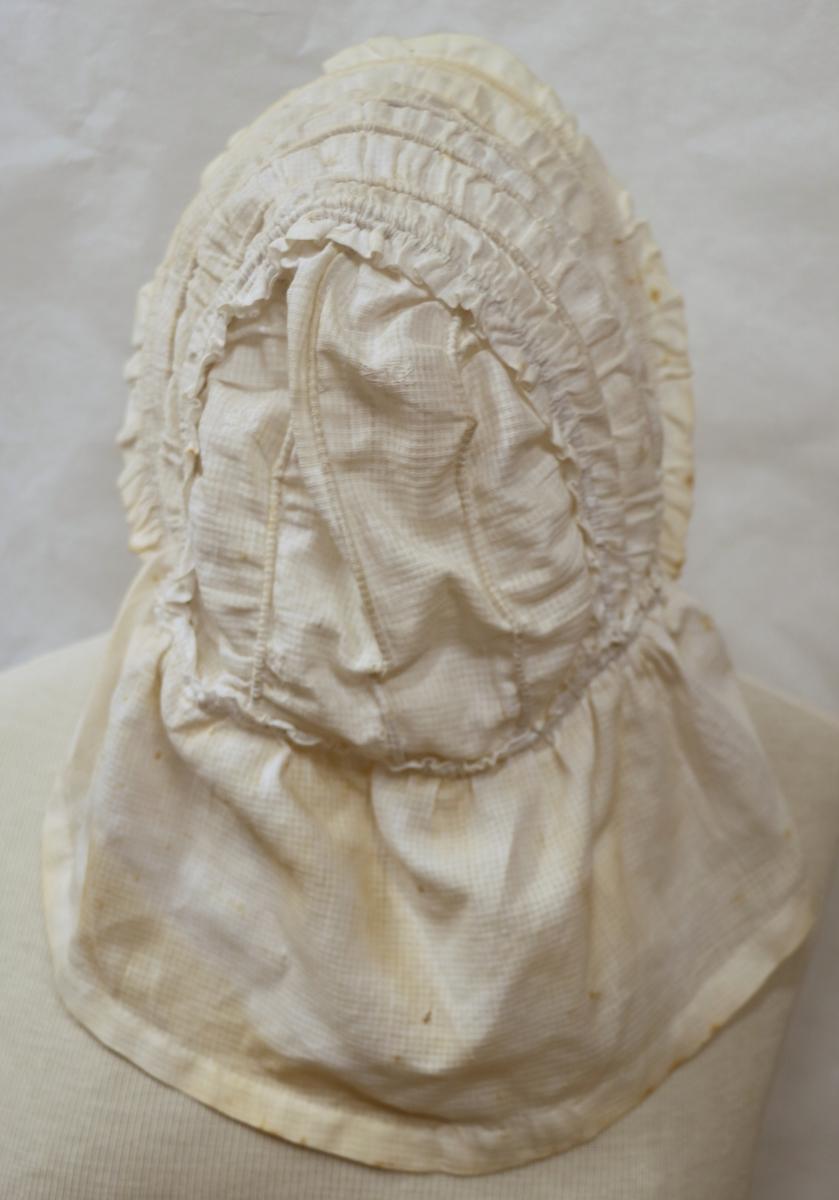 Rektangulært stykke med D-form avstivet med parallelle spiler, rynkekant om ansikt. Rynket skulderkappe, knytebånd.