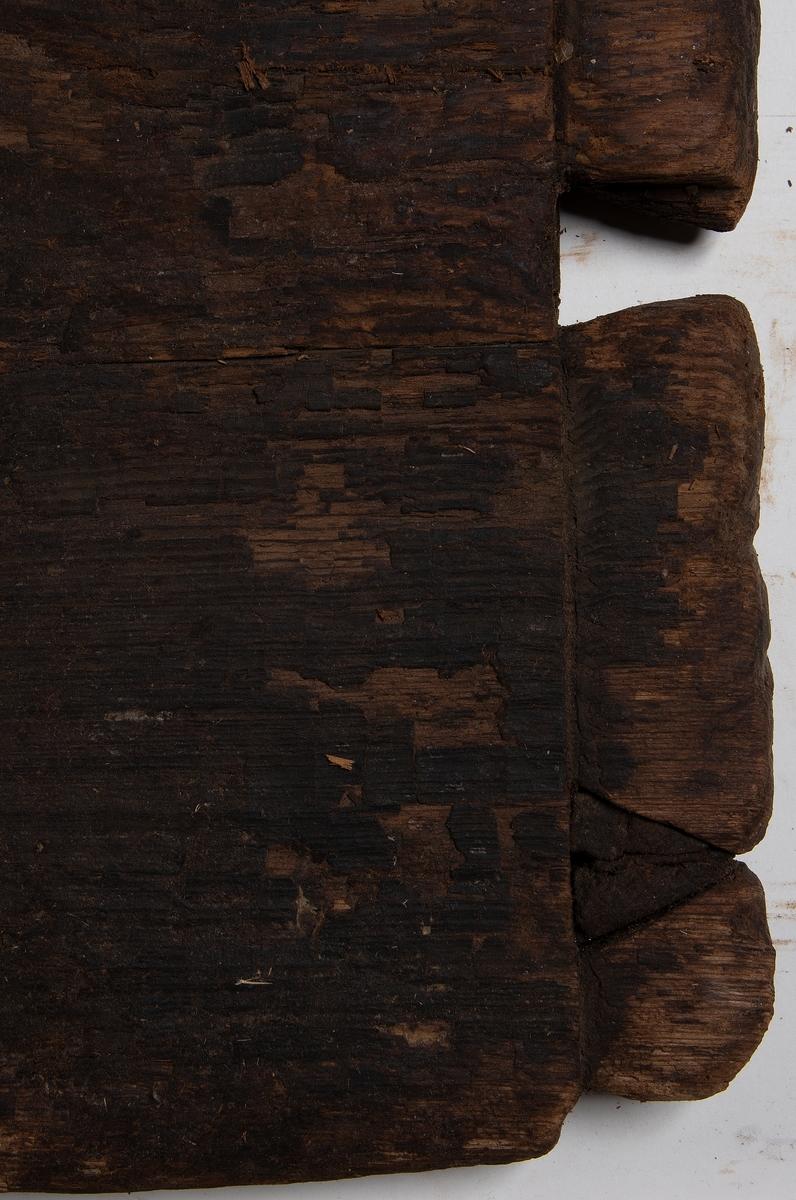 Planka. Ena långsidan delvis avspjälkad. Urtag i båda ändar, på den ena änden är urtagen laxstjärtformade.