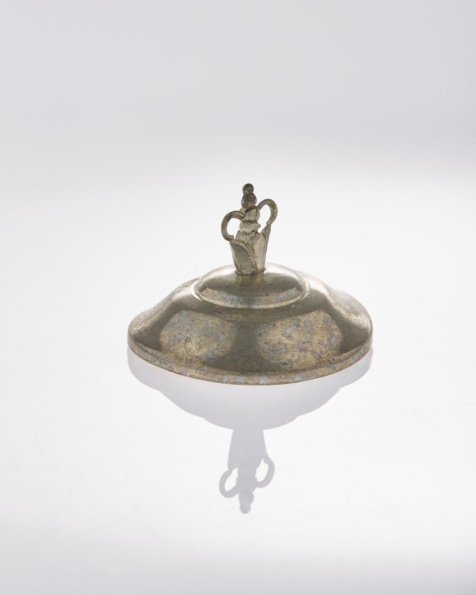 Lokk til pokal i tinn med en krone på toppen.
