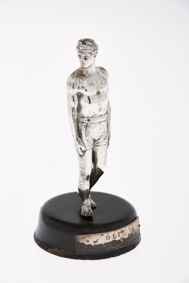 Statuett i sølvfarget metall, en atlet, med støtte i tre. Plakett på trestøtten med inskripsjon.