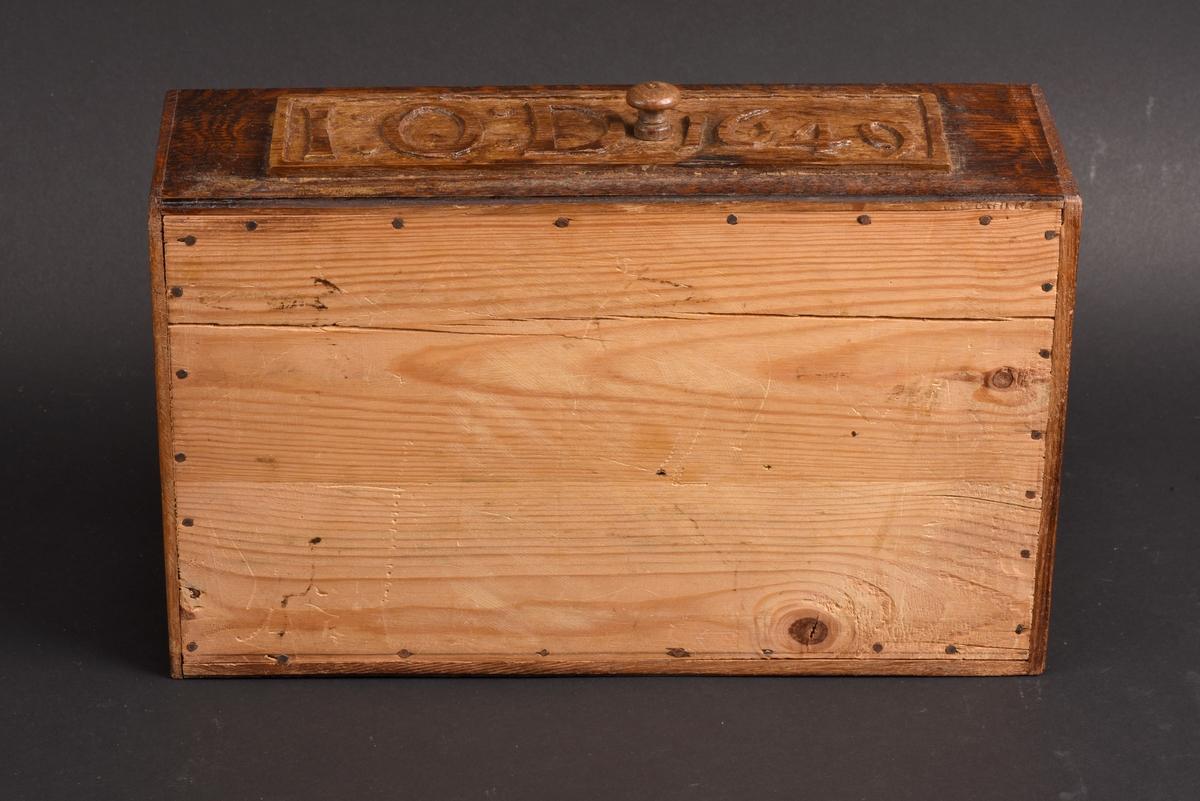 Rektangulärt skrin med lock. Skrinet tillverkat av ek, botten av furu. Locket är på undersidan försett med en låsmekanism bestående av små vridbara hjul. På ena långsidan är en äldre del infogad med initialerna IOD samt årtalet 1649.