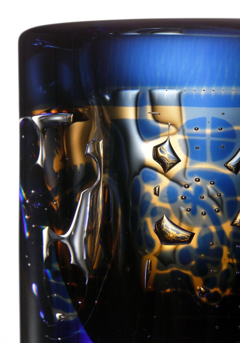 """Blå och gul vas """"Ariel"""" av Edvin Öhrström, försedd med ett luftmönster bestående av en man och en kvinna."""