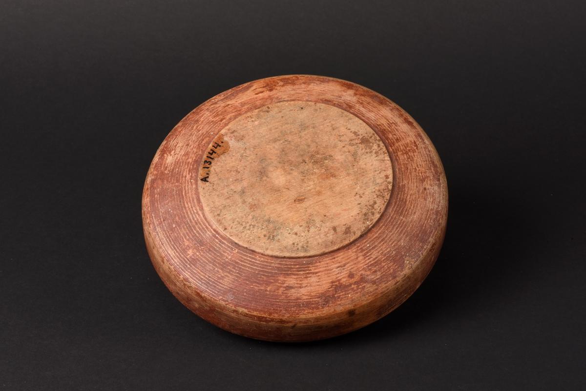 Rund svarvad smörask med lock, tillverkad av trä. Locket har en rektangulärt utskuren knopp som handtag.