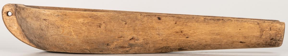 Ärtränna ytterkanten fasad plana ytor märkt N på undersidan. Urholkad ur ett avlångt trästycke.  Vid tjockänden ristat rutmönster.