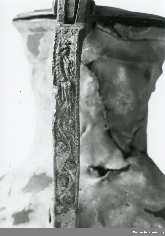 KLM 46428 Kanna av tenn. Bukig form. Hankkärl, försedd med lock och handtag, vidgad botten neråt. I botten, invändigt en medalj med korsfästelsebild. Medaljens kant försedd med pärlring. Ägarmärke/bomärke på lockets och bottens utsidor. Handtaget ornerat med drakmotiv och bladslinga, tumgreppet saknar ett av ekollonen. Kannan skadades svårt vid upphittandet, genomgående sprickor på många ställen.