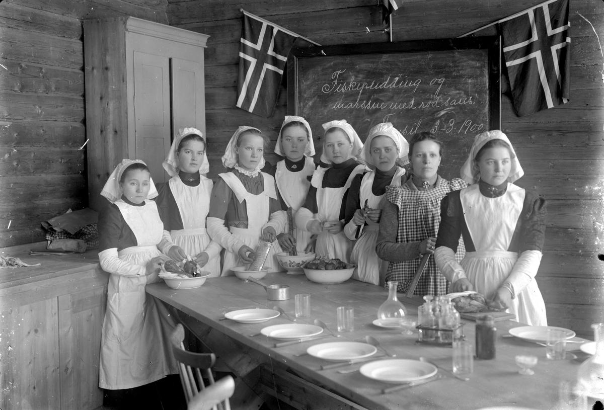 """Åtte jenter på husstellkurs foran tavle der det står """"Fiskepudding og marssne med rød saus. Trysil 3 -3 1900""""."""