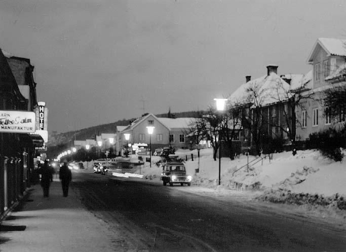 Brahegatan i kvällsljus vintertid. Gatubelysningen är tänd. Några flanörer på trottoaren till vänster. Mötande bilar på väg söderut. Skyltning för Folke Palms Garn & Manufaktur samt Hotell Ribbagården.