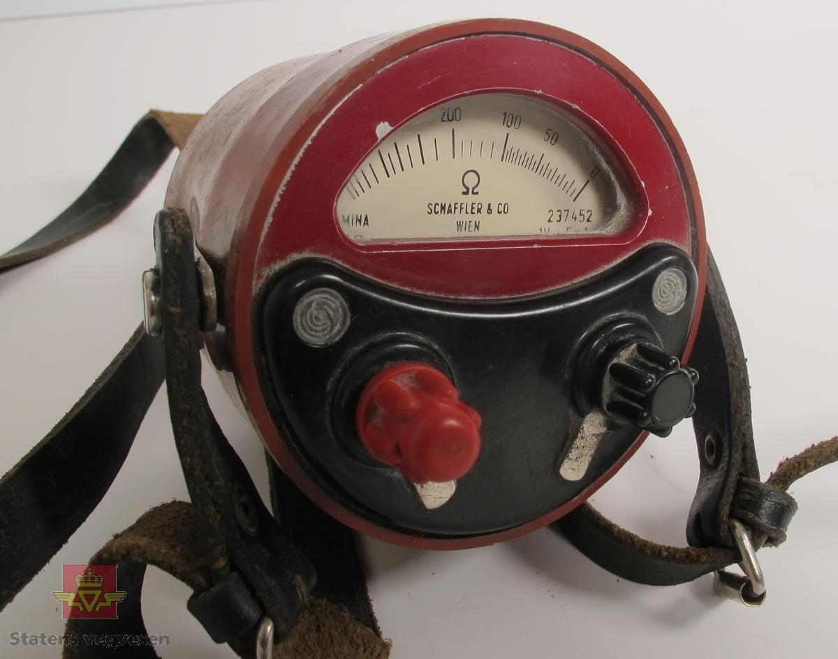 Ohmmeter i burgunderrødt hus av metall, dekket med gummi. Har to tilkoblingspunkter for ledning og bærereim av lær. Målevindu med nål som viser verdier fra 0 til 1000 ohm. Mangler lokk. Har påskriften DREMONIA 1970 SCHAFFLER & CO WIEN 237452 1V 5 mA i målevinduet på ohmmeteret.