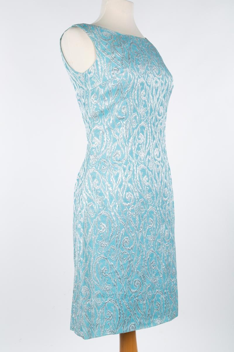 Selskapskjole med selskapsveske. Brokadevevet syntetisk stof, mønster i lysblå og sølv.   A: Kjolen helskåret i 3 bredder, buet halsringing, dyp buet rygg, rette sidesnitt, brytsnitt, glidelås midt bak. Uten ermer. Konfeksjon?, Omsydd. Opprinnelig lang, klippet av nederst. Reststoffet brukt til selskapsveske.   B: Vesken: pappkartong A4-ark brettet og trukket med stoffet fra kjolen. Metall lenker.  Giver: Astri Breder Berg, Oppegård