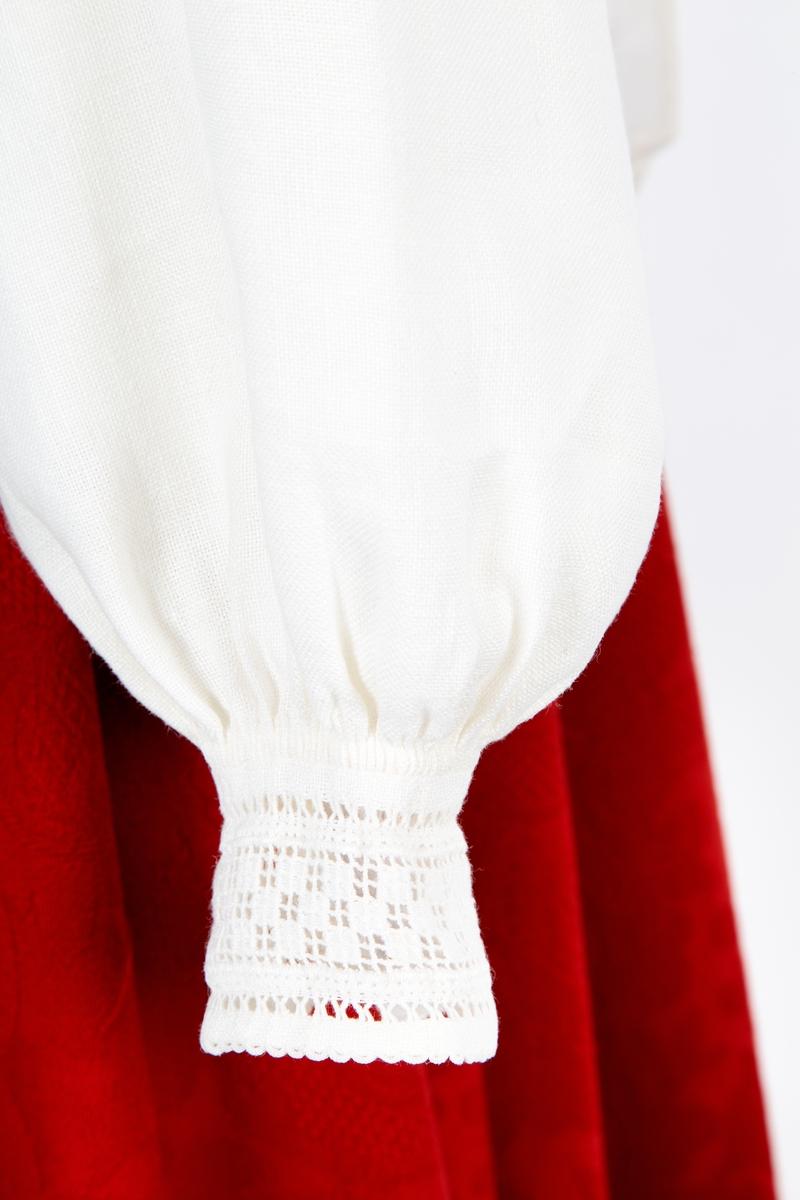 Bunadskjorte i lin. Uttrekksømbroderi på hals- og håndlinninger. Trådknapp og hempe på håndlinningene. Rynket og stripet vel hals og håndlinning. Små legg på ermet ved skulder. Halssplitt med hullfall.  Bunaden har skjorte i hvit lin. På halskragen og håndlinningen er broderi i dobbelt uttrekksøm. Forbildet for broderiet er en navneduk i lin fra Søndre Gjølstad i Såner, (Vestby). Skjorta lukkes med sølje i halsen og trådknapp og hempe ved håndleddet