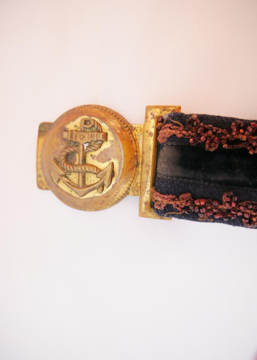 Mørkeblått belte med et svart fløyelsbånd midt på og to rader med brunrøde perler. En metallspenne med ankermotiv.