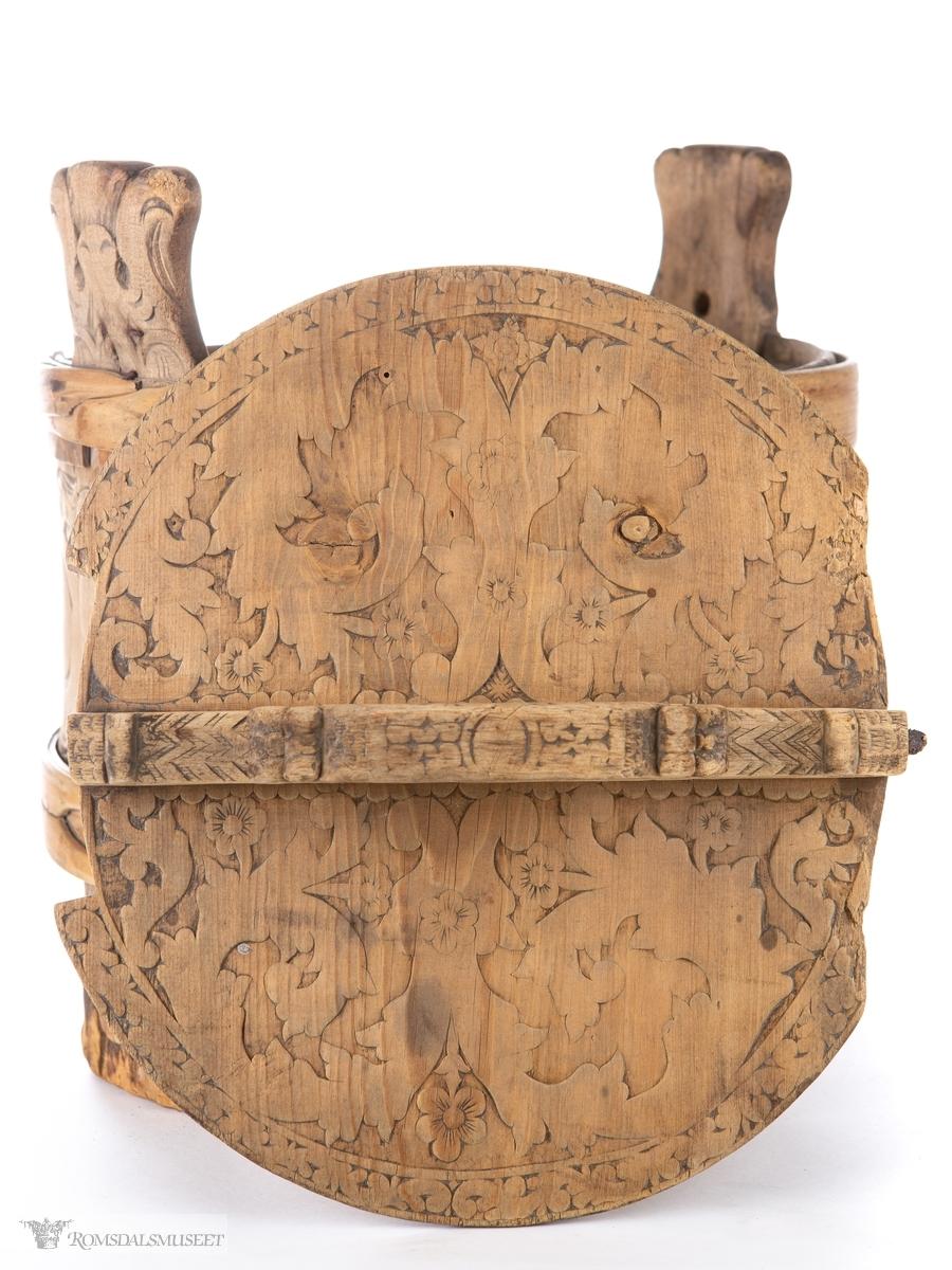 Utskårede stemorsblomster og blader i lav relieff på lokket. Tette akantusranker i lav relieff er skåret ut på alle ambarens staver.