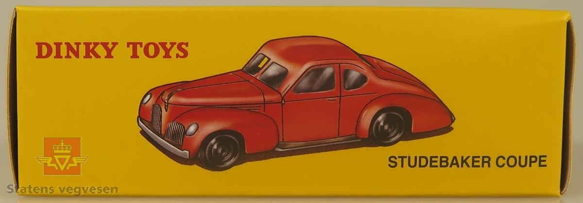 Modellbil av en Studebaker Coupe. bilen er grå med røde hujlkapsler.