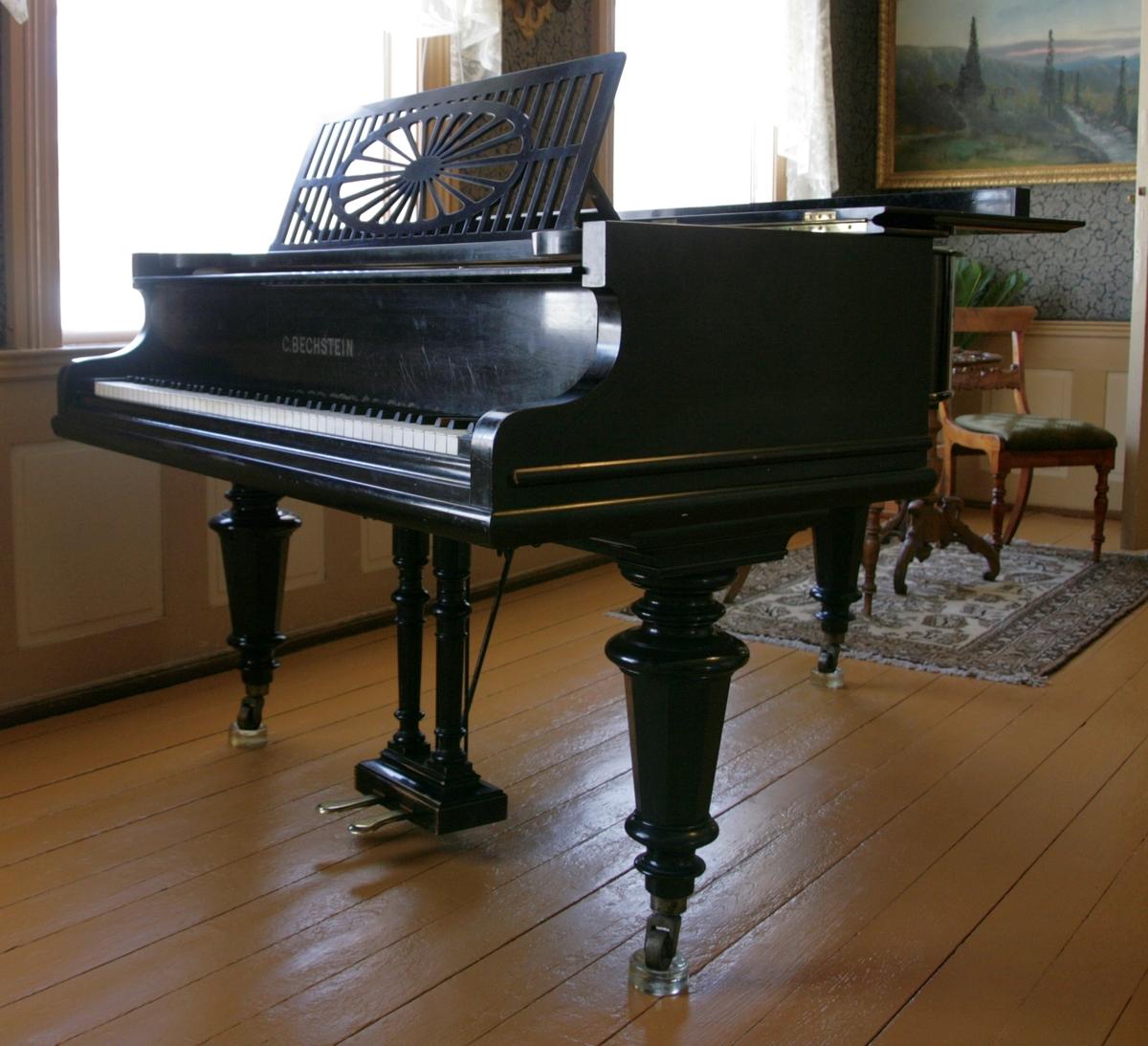 """Omfang: AAA-a'''' (7 oktaver) Svartmalt kasse. Tre ben. Lokk som kan åpnes. Notebrett som kan legges ned under lokket.  Helstøpt jernramme.  To pedaler: v. """"due corda"""" (piano); h. demperløft (forte). Dempere til og med d'''. AAA-AA (13 strenger) enkorig, med tettspunnet kobber om jern/stål BB-A (12 x 2 strenger) tokorig, med tettspunnet kobber om jern/stål B-a'''' trekorig, stål/jern."""