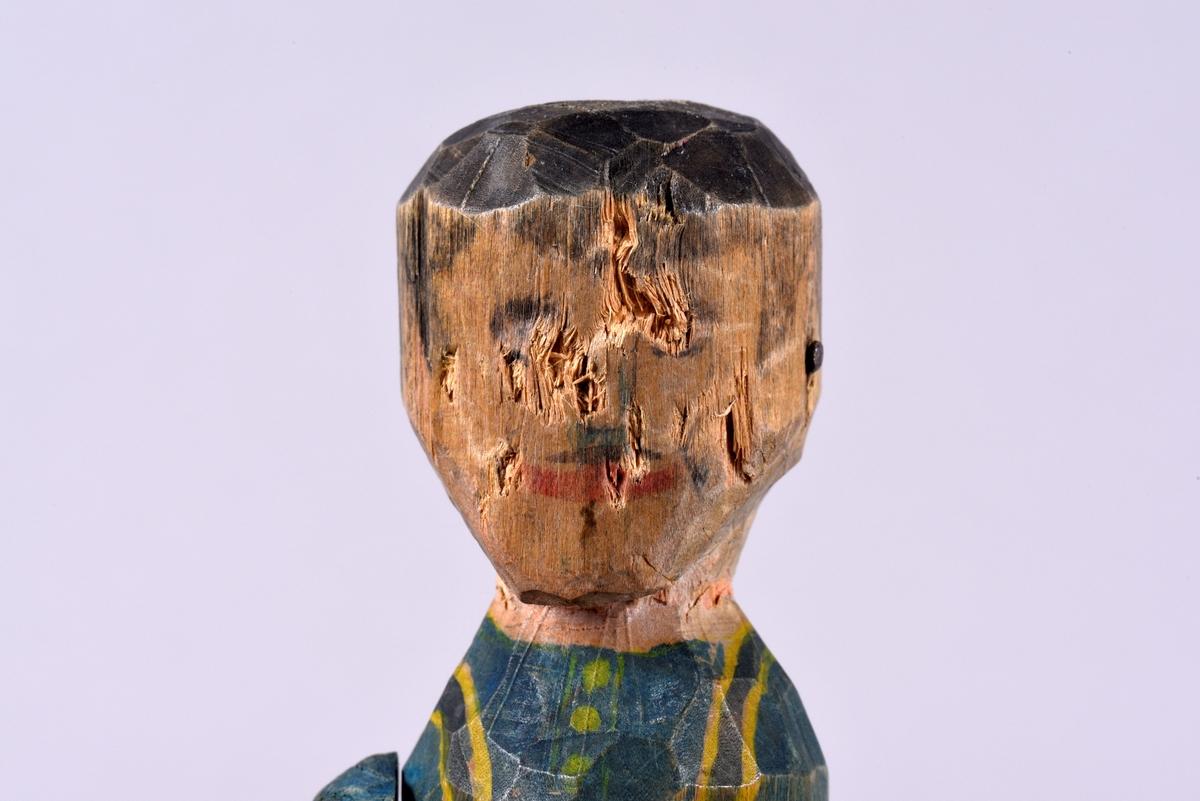 En skuren mansdocka av trä. Skuren i ett stycke, förutom armarna, varav en saknas. Bemålad med svart hår och mustasch samt kläder i blått, och ett förkläde med gula kanter.