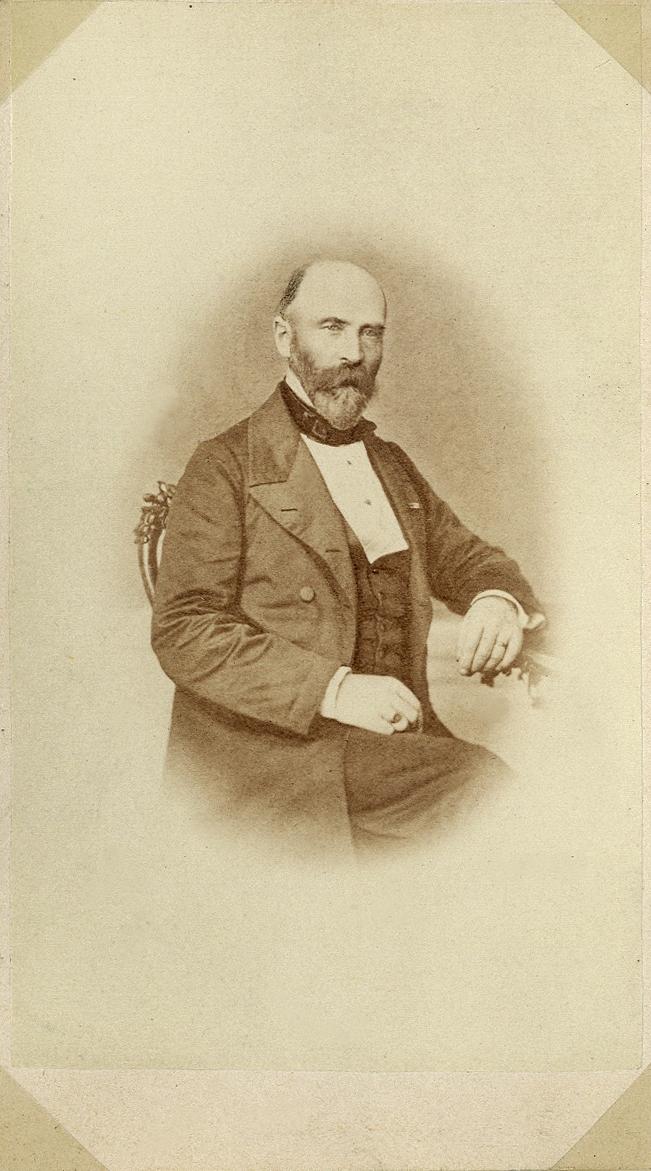 Porträttfoto av en skäggig man i bonjour med väst, stärkkrage och fluga.  Knäbild, halvprofil. Ateljéfoto.
