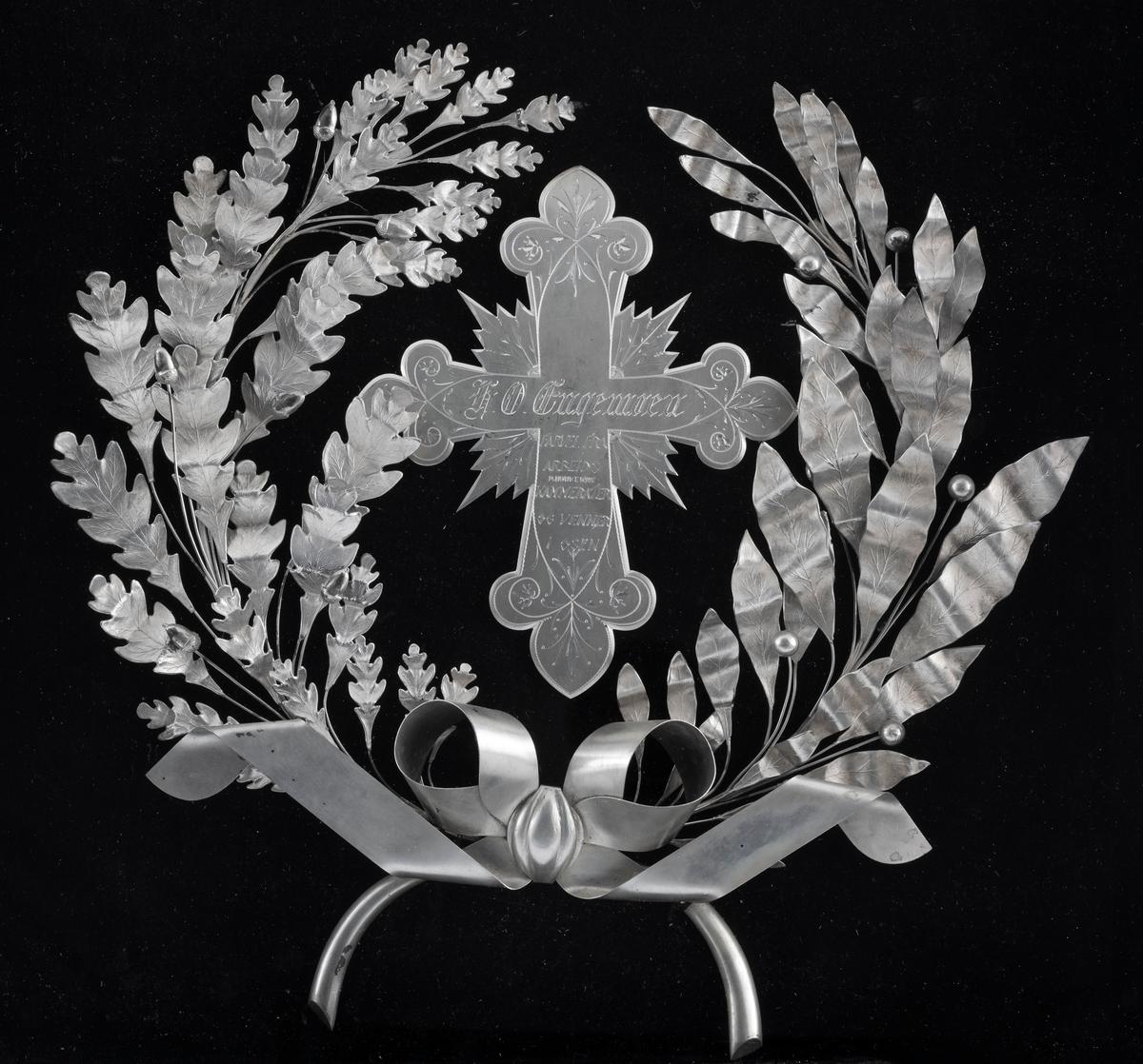 Gravminne, der noen elementer i sølv er ment å være de mest iøynefallende. Den mest sentrale av disse komponentene er et kors, der armene har treflikete avslutninger. Fra hjørnene der disse armene møtes «vokser» det ut spissflikete blader. Korsets ytterkanter har også symmetrisk rankegravyr. Sentralt på korset er følgende tekst inngravert: «H.O.Engemoen  FARVEL FRA ARBEIDSKAMERATER OG VENNER I OSEN». På begge sider av korset ligger det buete kvister - på den ene sida en eikekvist med nøtter og på den andre en kvist med mer spissovale blader og kuleformete fruktlegemer. De to kvistene møtes i ei stililsert sløyfe av tynne sølvband, plassert sentralt under korset. De beskrevne sølvornamentene er plassert på ei pute som er trukket med et svart, plysjliknende stoff. Hele montasjen ligger i ei svartmalt, nesten kvadratisk trekasse. Standflata er 42,5 centimeter bred og 42,8 centimeter høy. Lokket er 43,4 centimeter bredt og 43,8 centimeter høyt. Sjølve kassa er 40,2 centimeter bred og 40,8 centimeter høy. Høyden fra standflata til lokkets overkant er 10,9 centimeter i fronten og 15,5 centimeter i bakkant. I lokket er det ei glassrute - 34,8 X 35,0 centimeter - som gjør det mulig å se ned på sølvkomponentene på den svarte puta. I den fremre veggen på kassa er det et nøkkelhull. Nøkkelen later ikke til å være bevart.