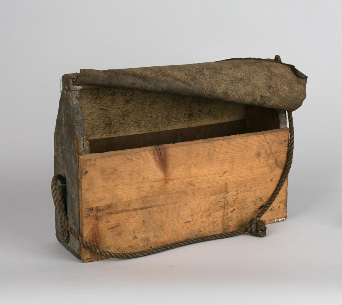 Verktøykasse i tre. Hjemmelaget med åpning i topp uten lokk, stoffstykke over åpning. Rektangulær med hank samt hampetau for å bære over skulder.