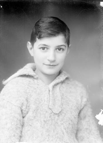 Porträtt av okänd mörkhårig pojk, bröstbild. Han har en stickad tröja med krage på sig.