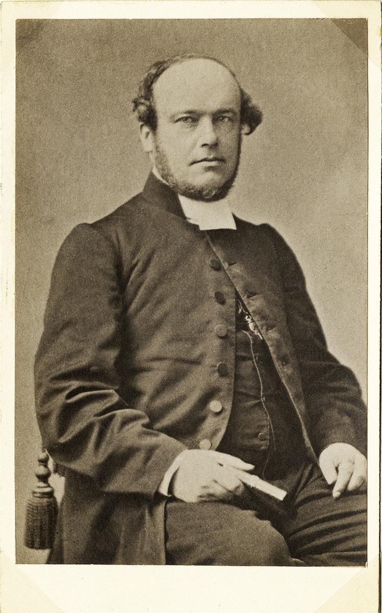 Foto av en man i prästrock med väst och prästkrage. Längs västen skymtar en klockkedja.  Han sitter på en stol med en bok i handen.  Knäbild, halvprofil. Ateljéfoto.