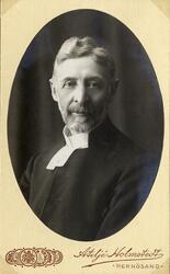 Foto av en skäggig man i prästrock och prästkrage. Bröstbild